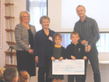 Mr Andy Simpson (PTA Chairperson) with school children handing over the cheque to CAFOD Schools Volunteers, Katherine Simpson and Pat Atha