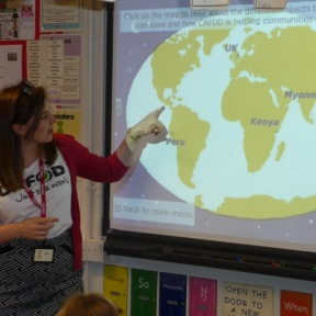 Sophie in school pointing at map